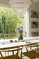 Dining area with pale wooden classic chairs, Enigma designer pendant lamp and view of bamboo bush through window in background