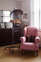 Retro studio lamp on castors and antique reading chair with pink upholstery next to window
