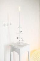 White interior: lit candles in romantic candelabra on plant stand