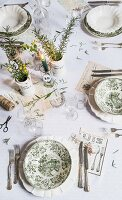 Table set with vintage toile de jouy plates, lit candle and vases of herbs