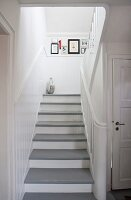 White wooden staircase with grey-painted treads in rustic stairwell