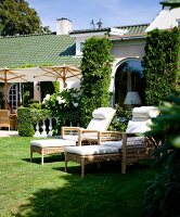 Pale wicker sun loungers with white cushions outside rustic house