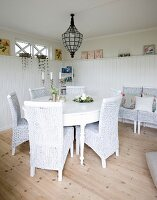 White wicker chairs at round table below vintage pendant lamp in corner of white, wood-clad dining room