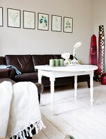 White-painted side table with turned legs in front of black leather couch below framed botanical pictures on wall