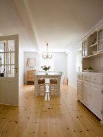 Dining room with white-painted chairs and table and rustic dresser on well-tended wooden floor