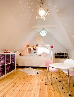 Nursery in converted attic; table with colourful chairs, bed below window and pendant lamp throwing pattern of lights on gable ceiling