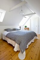 Black and white striped bedspread on double bed in white bedroom in renovated attic with wooden floor