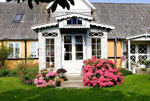 View from garden of pink hydrangeas flanking white-painted wooden porch of house