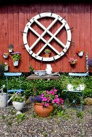 Old mill wheel and potted plants on Falu-red wooden wall behind garden furniture and flowers