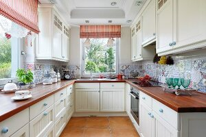 Modern, U-shaped fitted kitchen in country-house style with mixture of tiles on splashback, wooden worksurfaces and red and white striped roller blinds