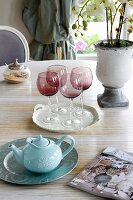 Red, smoked-glass wine glasses and teapot on dining table