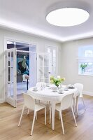 Large, round ceiling lamp above white dining set and view of modern artwork through open double glass doors