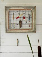 Various anglers' lures hung from wire mesh in vintage picture frame