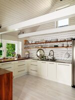 Pale, modern fitted kitchen in renovated country house with crockery on shelves and exposed, white roof beams