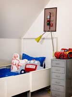 Boy's bedroom with white, extendible bed, scatter cushions, grey filing cabinet and standard lamp