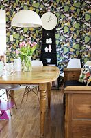 Wooden dining table below pendant lamp with white lampshade; long-case clock against leaf-patterned wallpaper in background
