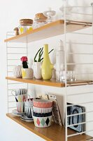 Crockery with colourful, retro patterns, vases and storage jars on wall-mounted String shelves