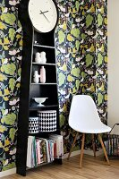 Long-case clock with shelves in black casing, tins with contrasting retro patterns, classic-style shell chair and leaf-patterned wallpaper