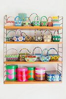 Collection of colourful beaded baskets and printed tins on wall-mounted String shelves
