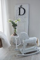 Old rocking horse next to vase of amaryllis on white-painted stool in front of decorative letter hung on removed door