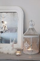 Ornamental birdcage candle lantern, white-framed mirror and china reindeer