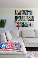 Comfortable reading area with ethnic rugs on designer sofa and photo art on wall