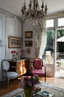 Rococo-style chairs next to chest of drawers in corner below crystal chandelier