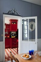 Dining table in front of open door and view of red-painted cabinets in kitchen