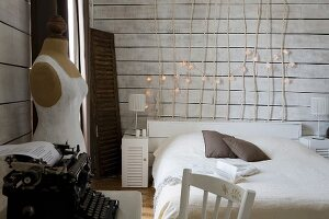 Simple bed with wooden headboard made of branches decorated with fairy lights, vintage typewriter and tailors' dummy in white, wood-clad bedroom