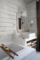 Modern bathtub next to masonry washstand in corner of bathroom with white wood-clad walls