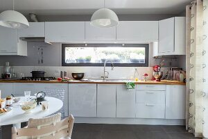 White fitted kitchen with ribbon window