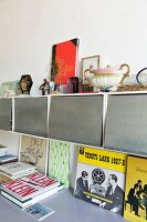 Collectors' items on top of wall-mounted cabinets above books on surface