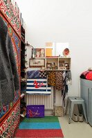Narrow bedroom with striped rug, retro metal stool and wardrobe with ethnic patterns painted on front