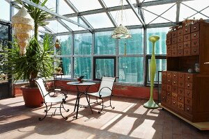 Vintage-style apothecary cabinet, pendant lamps and sunny seating area in conservatory