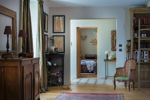 Table lamp on antique, rustic cabinet, antique cane armchair and doorway leading into bedroom