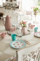 Table with painted chequered top set with romantic pastel crockery