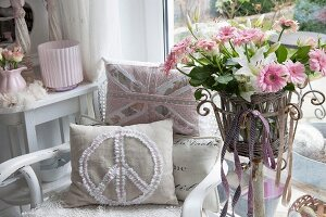 Cushions with romantic appliqué on armchair and pink gerbera daisies in wicker basket on plant stand next to large window