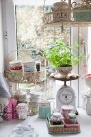 Floral bowls, home-made jams and vintage kitchen scales in front of window