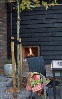 Dark wicker rattan chair and fire in outdoor fireplace on autumnal terrace