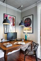 Modern black plastic chair at antique table below pendant lamps in corner of room with pale grey walls and white stucco frieze