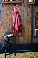Coat peg hand-crafted from books and hook on rustic wooden wall below bookshelves next to hat on black swivel stool