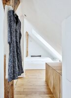 Dressing gown on coat hanger and cubby bed under sloping ceiling in converted modern attic room