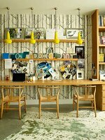 Long table and classic wooden chairs against study wallpaper with pattern of tree trunks