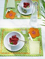 A place setting with raspberries and a homemade placemat with a floral pattern