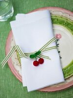 Linen napkin with ribbon and crocheted cherries on ceramic plate