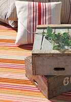 Stacked vintage wooden crates and striped cushions on striped rug