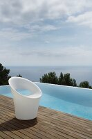 Designer chair made of white plastic on wooden deck next to infinity pool with sea view