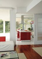 View from interior with exotic wood parquet through open sliding door into kitchen with red, central island counter