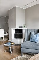 Sofa next to side table and open fireplace in interior painted pale grey