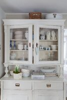 Crockery and spring flowers on and in shabby-chic dresser